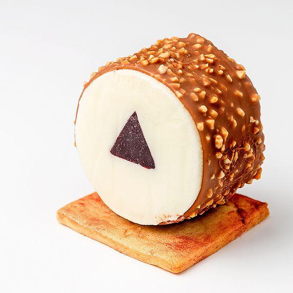 Postre helado de crujiente de chocolate y nada con núcleo de frambuesa sobre base para pasteles con forma cuadrada